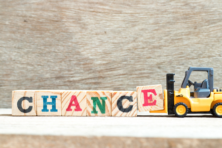 Toy forklift hold letter block E to complete word chance on wood background