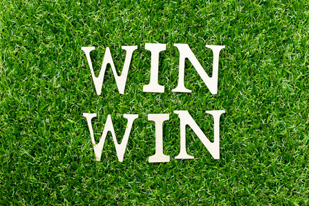 Wood alphabet letter in word win win on green grass background