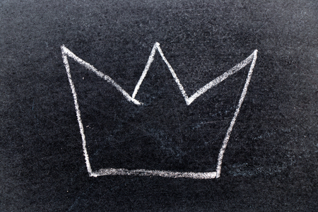 White chalk hand drawing in crown shape on black board background