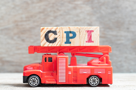 Red fire truck hold letter block in word CPI (abbreviation of consumer price index) on wood background
