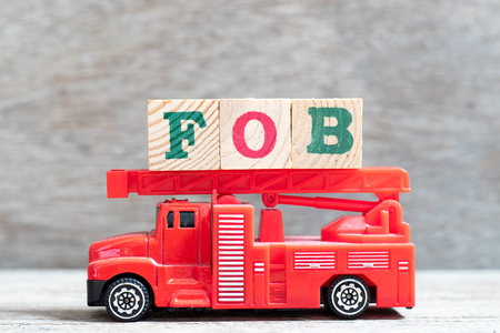 Red fire truck hold letter block in word FOB (Abbreviation of free on board) on wood background