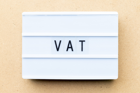 White lightbox with word VAT (Abbreviation of value added tax) on wood background Stock Photo