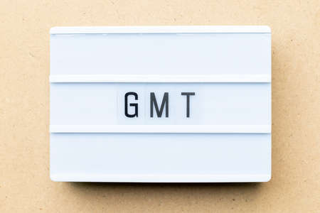 White lightbox with word GMT (abbreviation of Greenwich Mean Time) on wood background Foto de archivo
