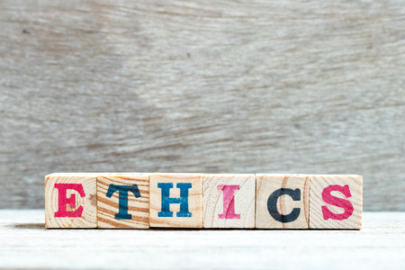 Alphabet letter block in word ethics on wood background
