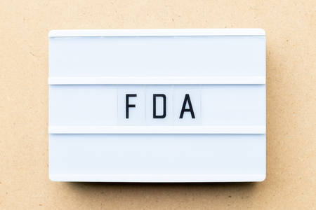 White lightbox with word FDA (abbreviation of food and drug administration) on wood background