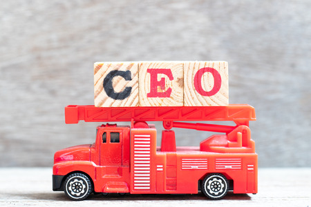Red fire truck hold letter block in word CEO (abbreviation of Chief Executive Officer) on wood background