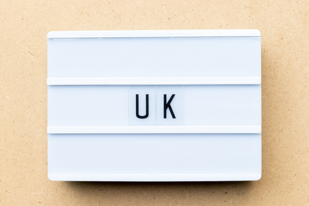White lightbox with word UK (abbreviation of united kingdom) on wood background