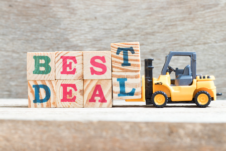 Toy forklift hold letter block t,l to complete word best deal on wood background