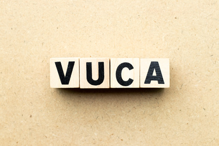 Letter block in word VUCA (abbreviation of Volatility, uncertainty, complexity and ambiguity) on wood background