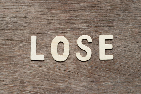 Alphabet letter in word lose on wood background