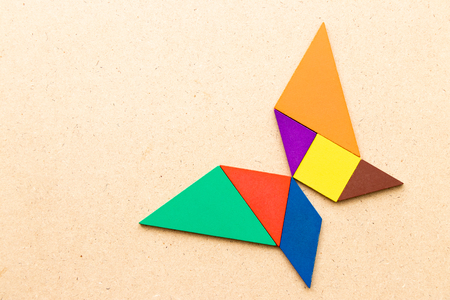 Color tangram in butterfly shape on wood background Banco de Imagens