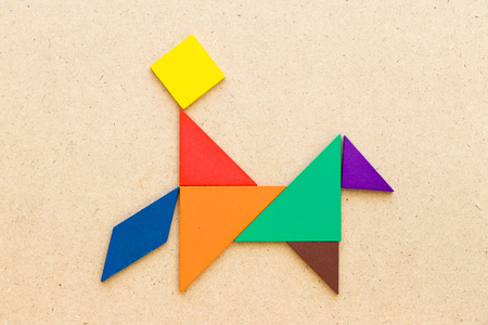 Color tangram puzzle in man ride on the horse shape on wood background