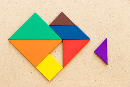 Color tangram puzzle in heart shape that wait triangle piece to fulfill on wood background Banco de Imagens