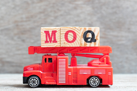 Red fire truck hold letter block in word MOQ (Abbreviation of Minimum Order Quantity) on wood background Banco de Imagens
