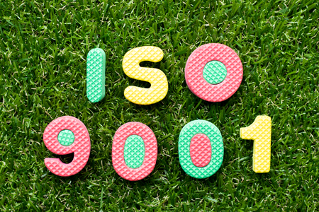 Toy foam letter in word iso 9001 on green grass background Reklamní fotografie