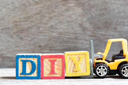 Toy forklift hold letter block Y to complete word DIY (abbreviation of do it yourself) on wood background