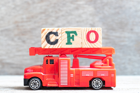 Red fire truck hold letter block in word CFO (Abbreviation of Chief Financial Officer) on wood background Reklamní fotografie
