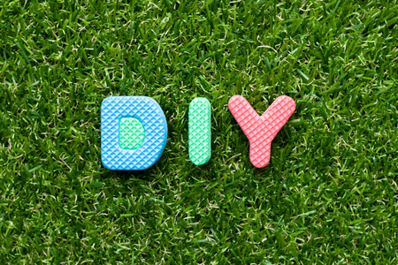 Toy foam letter in word DIY (abbreviation of do it yourself) on green grass background Banco de Imagens