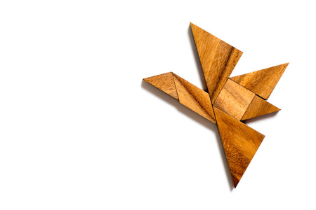Wood tangram puzzle in flying bird on white background Banco de Imagens