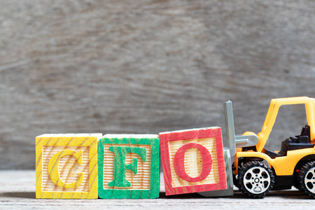 Toy forklift hold letter block O to complete word CFO (Abbreviation of Chief Financial Officer) on wood background Reklamní fotografie