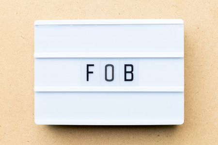 White lightbox with word FOB (Abbreviation of free on board) on wood background