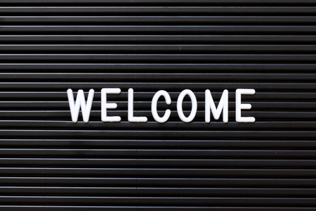 Black color felt letter board with white alphabet in word welcome background