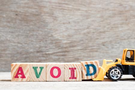 Topadora de juguete mantenga el bloque de letras d para completar la palabra evitar sobre fondo de madera