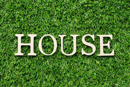 Wood alphabet letter in word house on green grass background Фото со стока