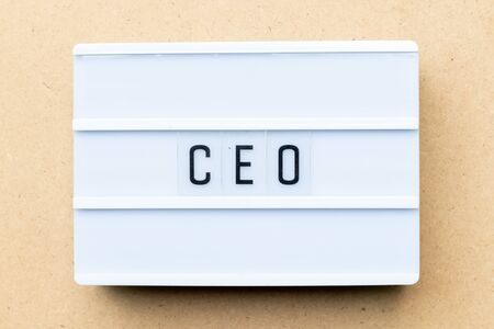 White lightbox with word CEO (abbreviation of Chief Executive Officer) on wood background