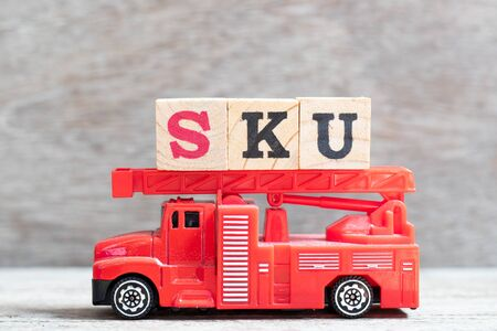 Red fire truck hold letter block in word SKU (abbreviation of stock keeping unit) on wood background Reklamní fotografie