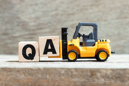 Toy forklift hold letter block a to complete word (Abbreviation of Quality Assurance or question and answer)on wood background Reklamní fotografie