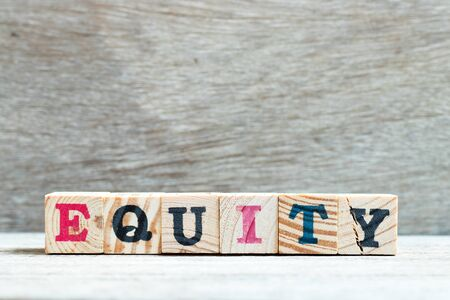 Letter block in word equity on wood background