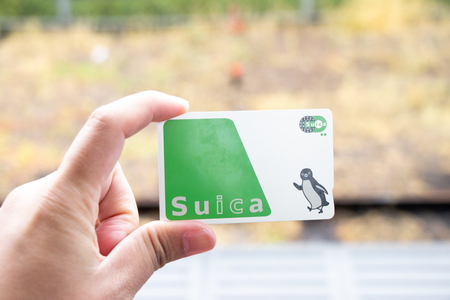 Tokyo, Japan - April 30, 2019 : Man hold Suica pass with the blurred background, Suica is a prepaid card for travelling with train, bus and shopping in Japan. Фото со стока - 124583107