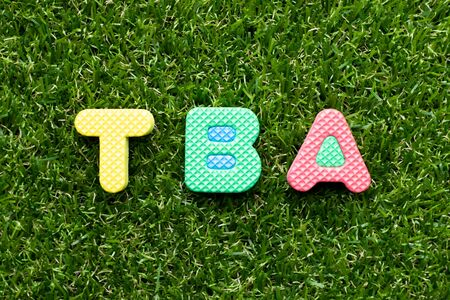 Toy foam letter in word TBA (abbreviation of to be announced)  on green grass background