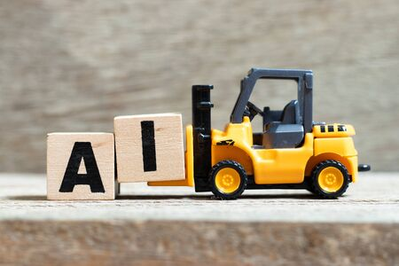 Toy forklift hold letter block i to complete word AI (Abbreviation of Page artificial intelligence) on wood background