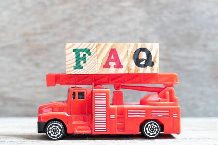Red fire truck hold letter block in word FAQ (Abbreviation of Frequently Asked Questions) on wood background