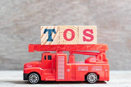 Red fire truck hold letter block in word TOS (abbreviation of Terms Of Service) on wood background