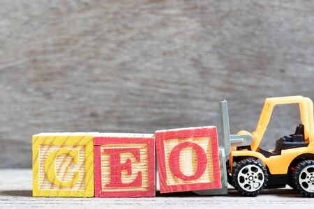 Toy forklift hold letter block O to complete word CEO (abbreviation of Chief Executive Officer) on wood background