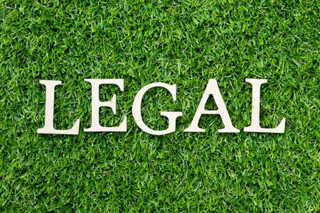 Wood alphabet letter in word legal on green grass background