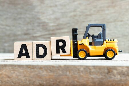 Spielzeuggabelstapler halten den Buchstabenblock r, um das Wort ADR (Abkürzung für unerwünschte Arzneimittelwirkung) auf Holzhintergrund zu vervollständigen Standard-Bild