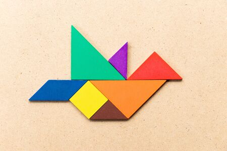 Color tangram puzzle in flying bird shape on wood background
