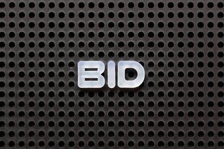 Black color pegboard with white letter in word bid Standard-Bild