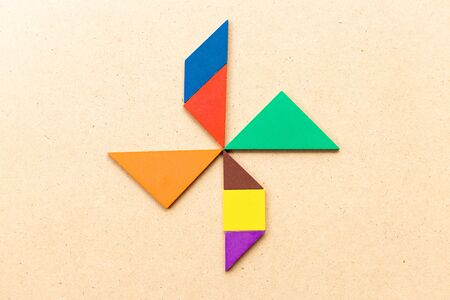 Color tangram puzzle in turbine, wheel or windmill shape on wood background