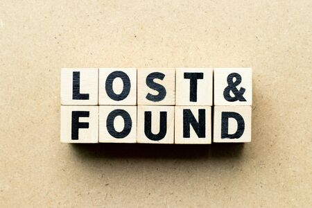 Bloc de lettres dans le mot perdu et trouvé sur fond de bois Banque d'images