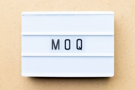 White lightbox with word MOQ (Abbreviation of Minimum Order Quantity) on wood background Banco de Imagens