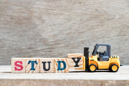 Toy forklift hold letter block y to complete word study on wood background