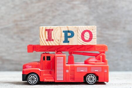 Red fire truck hold letter block in word IPO (Abbreviation of Initial Public Offering) on wood background Stock Photo