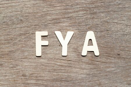 Alphabet letter in word FYA (Abbreviation of For your action or attention) on wood background