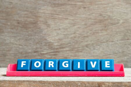 Tile letter on red rack in word forgive on wood background Imagens