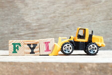 Toy bulldozer hold letter block I to complete word FYI (Abbreviation of For your information) on wood background Stok Fotoğraf